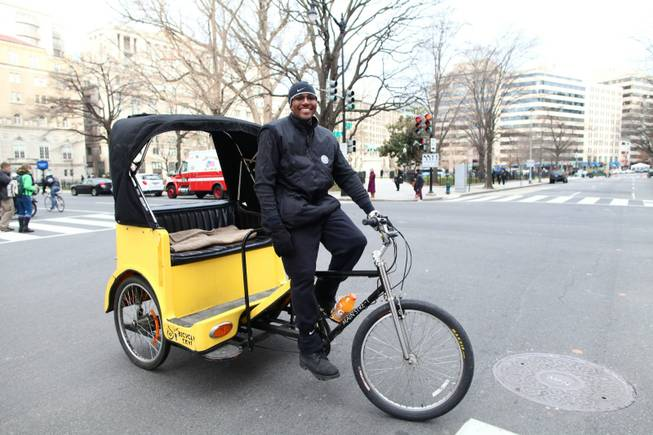 Kevin Bonner rides his pedicab at the corner of 15th and H Streets NW in Washington, D.C. after dropping off a customer on Inauguration Day, Monday, Jan. 21, 2013.