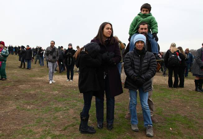 Corina Gonzalez and her husband Mark Pineda with their three kids, Olivia in the foreground, Nicolas on Pineda's shoulders, and Sophia, huddled against her mother, on the National Mall to watch the presidential inauguration ceremonies Monday, Jan. 21, 2013.