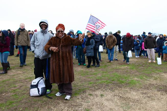 Lynnette Lynn-Horton of Capitol Heights, joined by her son Jordan Coleman, waves an American flag with Barack Obama's likeness on it while watching the presidential inauguration on the National Mall Monday, Jan. 21, 2013.