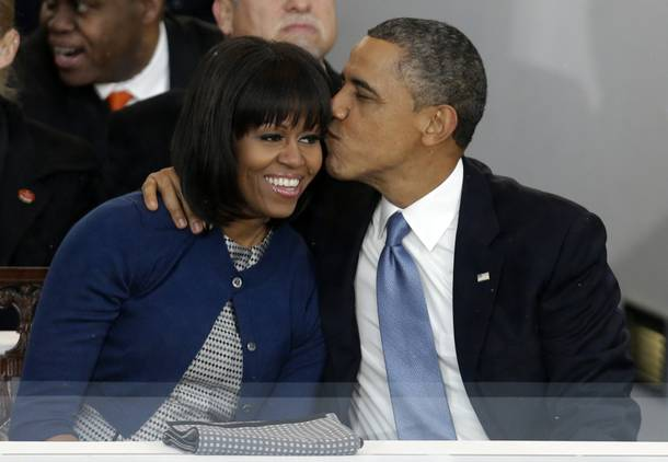 President Barack Obama kisses first lady Michelle Obama in the presidential box near the White House, Monday, Jan. 21, 2013, in Washington. Thousands  marched during the 57th Presidential Inauguration parade after the ceremonial swearing-in of President Barack Obama.