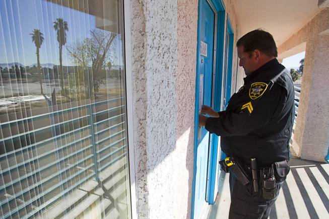 Deputy Constable Patrick Geary tapes a 24-hour eviction notice on the door of an apartment in the southwest Las Vegas Valley on Tuesday, Jan. 22, 2013. Apartment managers can post the notice themselves but often hire a constable.