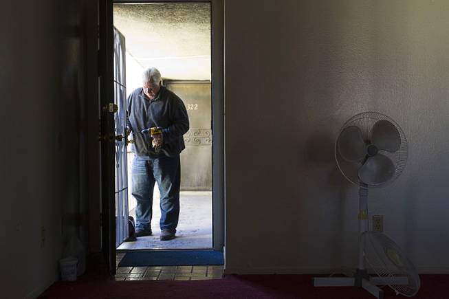 Joe Ingersoll, of All American Locksmiths, changes the lock on a security door during an eviction in the southwest part of the Las Vegas Valley Tuesday, Jan. 22, 2013.