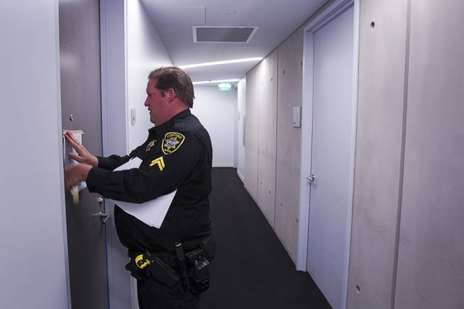 Deputy Constable Patrick Geary posts an eviction notice on a door of a condo in the Veer Towers Tuesday, Jan. 22, 2013.