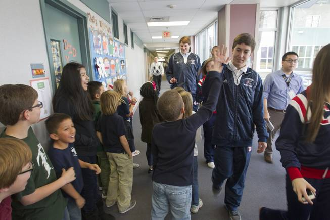 Students give high fives to Coronado High School basketball players and cheerleaders as the high schoolers arrive to mentor first- and second-graders at Glen Taylor Elementary School in Henderson on Wednesday, Jan. 23, 2013.