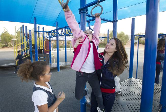 Coronado High School cheerleader Taylor Lewis assists first-grader Emily Neilsen on the playground at Glen Taylor Elementary School in Henderson on Wednesday, Jan. 23, 2013. Coronado basketball players and cheerleaders take time out of their season to mentor first- and second-graders at the school.