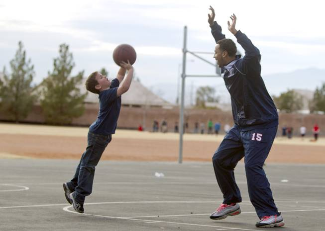 First grader Nolan Roos shoots over Coronado High School basketball player Jordan Willis during a one-on-one game on the playground at Glen Taylor Elementary School in Henderson on Wednesday, Jan. 23, 2013. Coronado basketball players and cheerleaders take time out of their season to mentor first- and second-graders at the school.