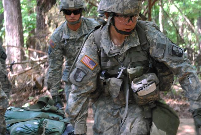 In a May 9, 2012, file photo, Capt. Sara Rodriguez, 26, of the 101st Airborne Division, carries a litter of sandbags during the Expert Field Medical Badge training at Fort Campbell, Ky.