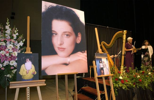 In this May 28, 2002, file photo, photographs of Chandra Levy are on display as musicians, right, stand by at a memorial service for Levy at the Modesto Centre Plaza in Modesto, Calif.