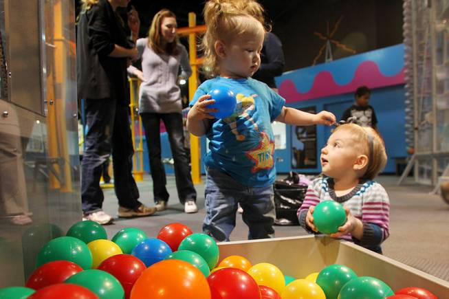Eve Ostro, left, and Audrey Wade play with plastic balls and each other at Lied Discovery Childrens Museum Saturday, Jan. 26, 2013.