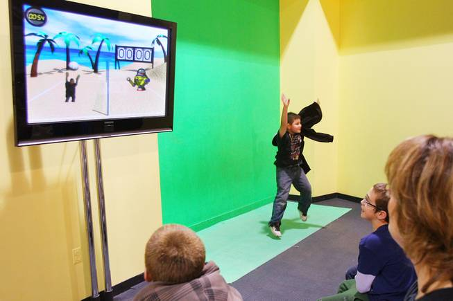 Christopher Leafdale interacts with a green screen and volleyball game at Lied Discovery Children's Museum Saturday, Jan. 26, 2013.