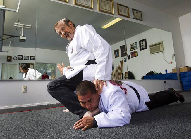 Karate master Dan Sawyer demonstrates a move on instructor Mauro Felix, a fifth degree black belt, during a class at his home Sunday, Jan. 27, 2013. Sawyer teaches in a garage behind his home that has been converted into a karate dojo.