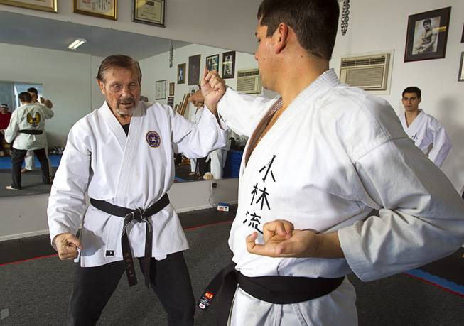 Karate master Dan Sawyer, left, demonstrates a technique with instructor Andy Dowdell, a fifth degree black belt, during a class at his home Sunday, Jan. 27, 2013. Sawyer teaches in a garage behind his home that has been converted into a karate dojo.