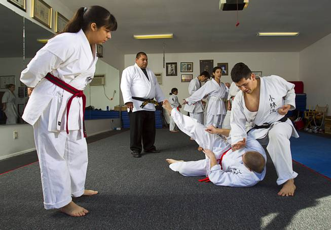 Student Abril Becerra, 14, looks on as Shorin-ryu karate instructor Andy Dowdell, a fifth degree black belt, demonstrates a take-down technique on student Mikel Hansen, 17, during a class at his home Sunday, Jan. 27, 2013. S