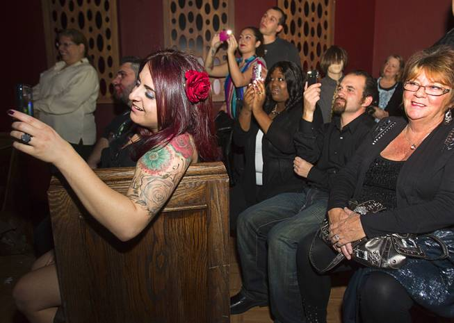 Friends and family members take photos as Anthony Gallegos and Rosie Grasso of Las Vegas get married in the chapel at Eli Roths Goretorium Sunday, Jan. 27, 2013.