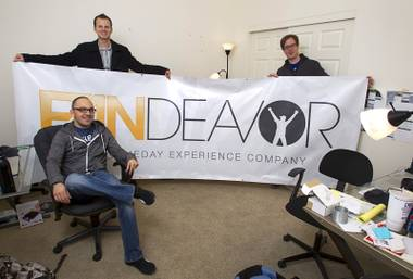 Company co-founders Tom Ellinson, left, and Dean Curtis pose with content manager Darren Flores, seated, at the Fandeavor offices in the Ogden in downtown Las Vegas Monday, Jan. 28, 2013. Fandeavor is a sports marketing group that sells special game-day packages to fans.