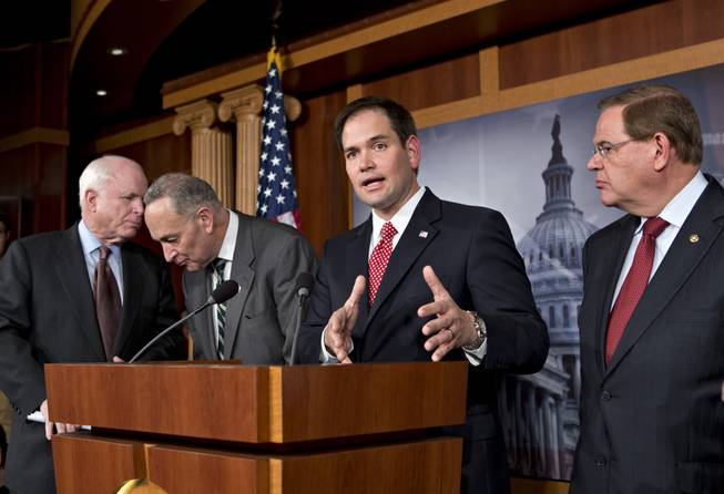 Sen. Marco Rubio, R-Fla.. center, answers a reporter's question as a bipartisan group of leading senators and he announce that they have reached agreement on the principles of sweeping legislation to rewrite the nation's immigration laws during a news conference at the Capitol in Washington, D.C., on Monday, Jan. 28, 2013. From left are Sen. John McCain, R-Ariz., Sen. Charles Schumer, D-N.Y., Rubio and Sen. Robert Menendez, D-N.J.