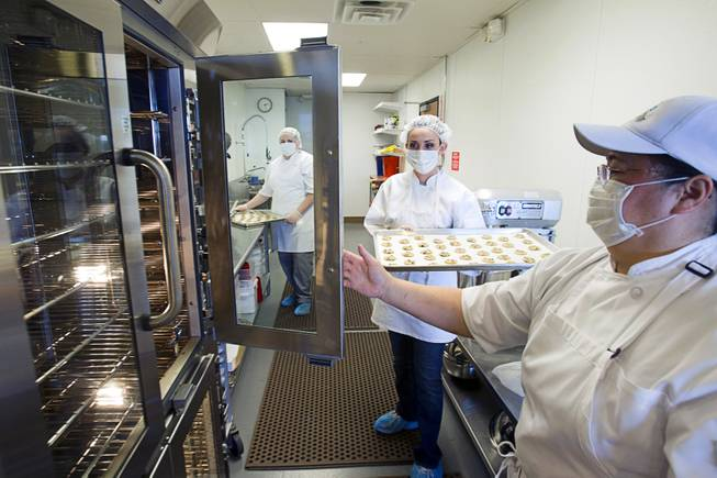 Jane Lee, right, owner and president of Jadon Foods, holds an oven door for Ahsley Money at the bakery with a tray of gluten-free cookies Wednesday, Jan. 30, 2013. Jadon Foods is a gluten-free bakery that also specializes in diabetic-friendly and dairy-free baked goods.