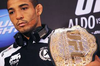 Jose Aldo carries his lightweight championship belt during the news conference for UFC 156 Thursday, Jan. 31, 2013.