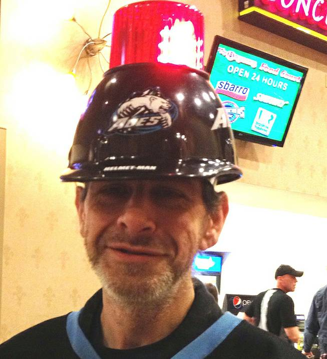 "Alaska Aces fan Rick White proudly wears his gear that earned him the nickname ""Helmet Man,"" Friday, Feb. 1, 2013, at the Orleans Arena. The Wranglers topped the aces 5-4."