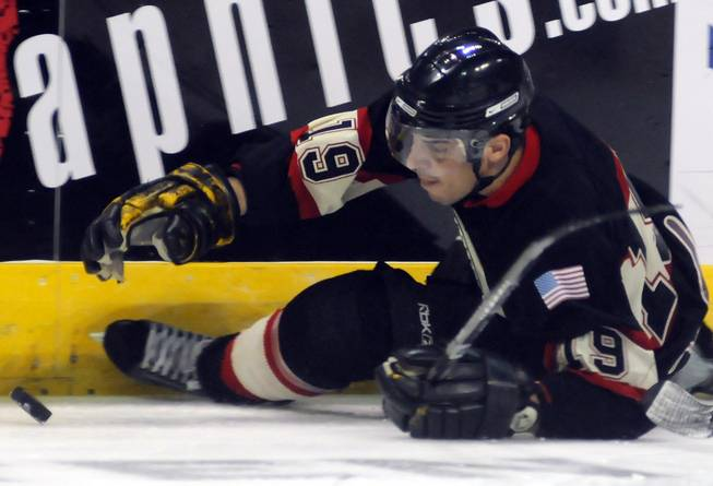 Las Vegas Valley fire player Kevin Fourman reaches for a fluttering puck after losing an edge near the boards during the second period of the Guns and Hoses Winter Classic 2013 on Saturday afternoon at the Orleans Arena.