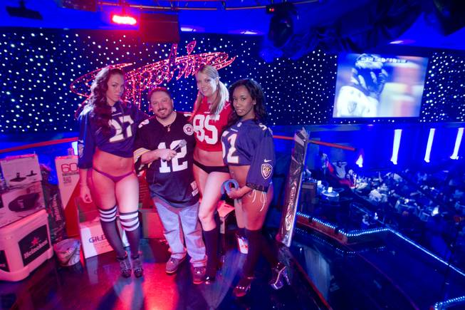 Disc jockey J.T. poses with Jersey Girls, from left, Hazel, Shauna and Passion Lee during a Super Sunday party at the Sapphire Las Vegas strip club Sunday, Feb. 3, 2013.