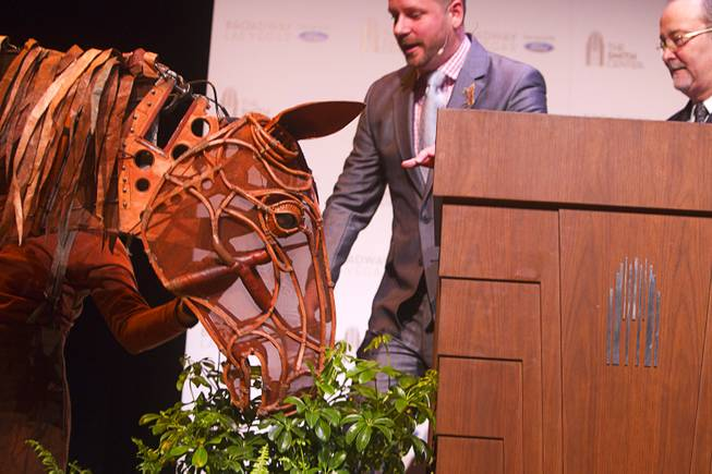 "Joey, the puppet horse from ""War Horse,"" appears to eat a potted plant during a donors reception at The Smith Center for the Performing Arts on Monday, Feb. 4, 2013. Scott Tucker of ""War Horse"" and Smith Center President and CEO Myron Martin are pictured with Joey."