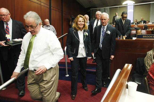 Assemblywoman Marilyn Kirkpatrick heads back to her desk after shooing members of the media away from Assemblyman Steven Brooks on the first day of the 2013 legislative session Monday, Feb. 4, 2013 in Carson City.
