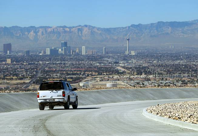 A sport utility vehicle drives down a paved channel on the Sunrise Landfill during a media tour Tuesday, Feb. 5, 2013. In 1998, a storm damaged the landfill cap, sending waste into the Las Vegas Wash and Lake Mead. The tour marked the completion of $36 million in storm control construction.