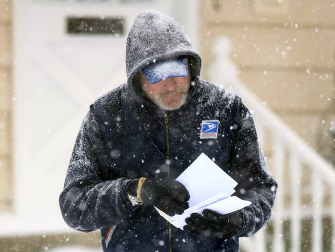 In this Saturday Dec. 19, 2009, file photo, U. S. Post Office letter carrier Tim Bell delivers the mail during a snow storm in Havertown, Pa.