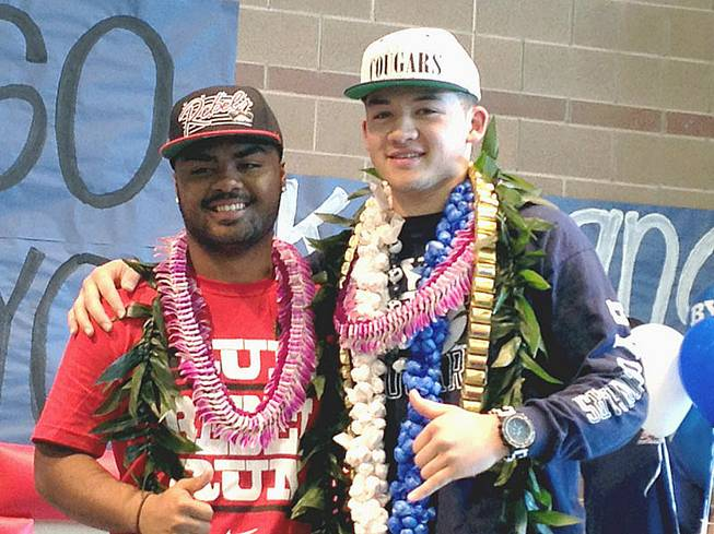 Liberty football players Niko Kapeli, left, and Kai Nacua are shown together after signing national letters of intent Wednesday, Feb. 6, in their school's gymnasium.