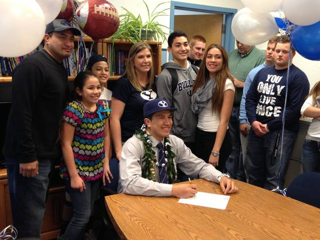 Centennial defensive end Trajan Pili signs his letter of intent to play for Brigham Young University with his family by his side on Wednesday February 6.