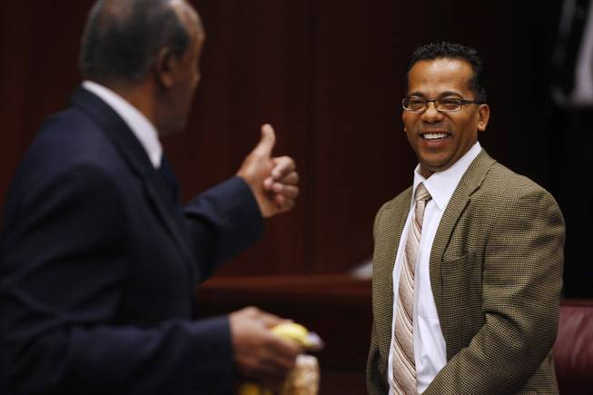Assemblyman Steven Brooks gets a thumbs up from Assemblyman Harvey Munford after talking with him before a floor session Thursday, Feb. 7, 2013 during the 2013 legislative session in Carson City.