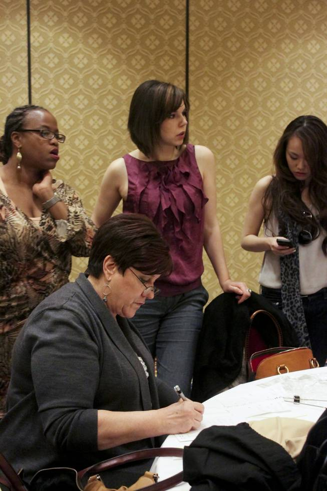 Fashion design students from the International Academy of Design & Technology (IADT), from left, Antoinette Rodchester, Dori Johnson and Mengxi Wang stand behind their teacher Carol Franklin during a dress reheasal fitting, Friday, Feb. 8, 2013.  IADT fashion students were commissioned by the American Renters Association to design formal wear using tablecloth fabric for a fashion show held Saturday, Feb. 9, 2013.