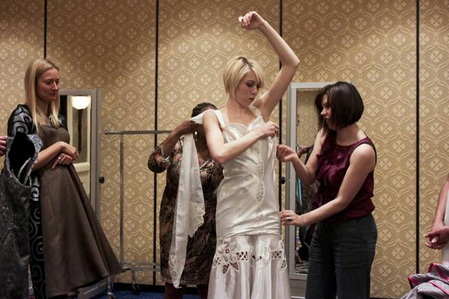 International Academy of Design & Technology (IADT) student Dori Johnson, right, fits a white dress designed by Ana Vea on model Katelyn Koval during a fashion show dress rehearsal, Friday, Feb. 8 2013.   IADT  fashion design students were commissioned by the American Renters Association to design formal wear using tablecloth fabric for a fashion show held Saturday, Feb. 9, 2013.