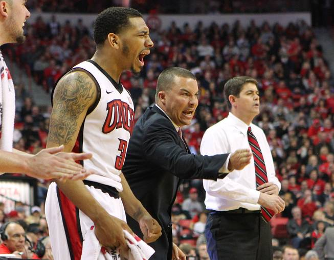 UNLV guard Anthony Marshall and assistant coach Justin Hutson cheer on the Rebels during their game against  New Mexico Saturday, Feb. 9, 2013 at the Thomas & Mack Center. UNLV beat New Mexico 64-55.