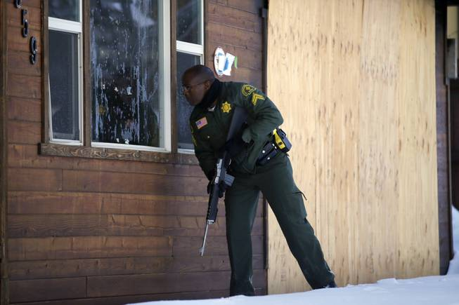 San Bernardino County Sheriff's officer Ken Owens searches a home for former Los Angeles police officer Christopher Dorner in Big Bear Lake, Calif., on Sunday, Feb. 10, 2013. The hunt for the former Los Angeles police officer suspected in three killings entered its fourth day in the snow-covered mountains on Sunday, a day after the police chief ordered a review of the disciplinary case that led to the fugitive's firing and new details emerged of the evidence he left behind.