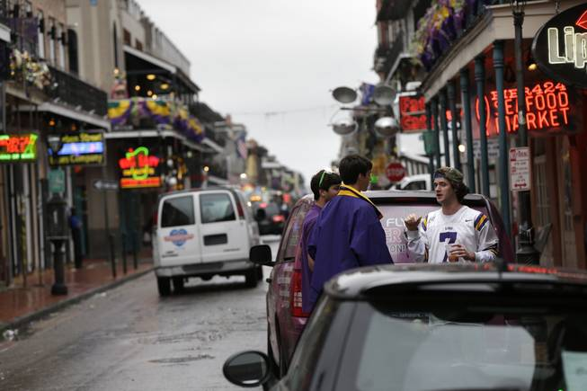 People walk near the 400 block of Bourbon Street in the French Quarter in New Orleans on Sunday, Feb. 10, 2013.