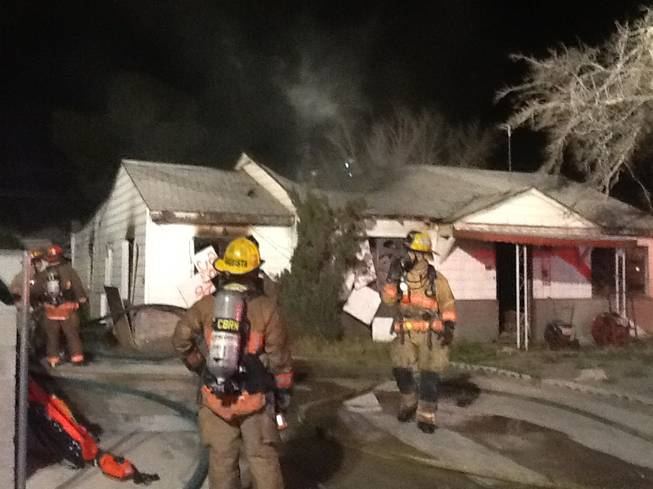 Firefighters work to extinguish an early-morning fire Sunday at a vacant downtown home.