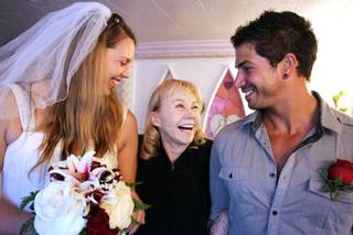 Charolette Richards, center, the owner of A Little White Wedding Chapel, laughs with newly married couple Elizabeth Hooker and Johnny Mitchell of Hong Kong inside the chapel in Las Vegas on Tuesday, February 12, 2013.