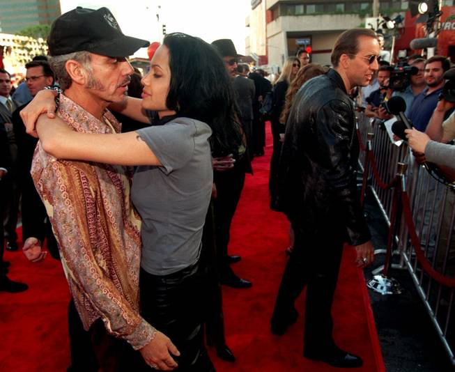"Actress Angelina Jolie, one of the stars of the new action film ""Gone in 60 Seconds,"" nuzzles with her husband, actor Billy Bob Thornton, as her co-star Nicolas Cage, at right, speaks to reporters at the premiere of the film, Monday, June 5, 2000, in the Westwood section of Los Angeles."