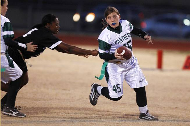 Palo Verde quarterback Kaitlyn Millican scrambles out of the reach of Silverado's Daiva Kempfer during the district championship for flag football Wednesday, Feb. 13, 2013. Palo Verde won the game 7-6.