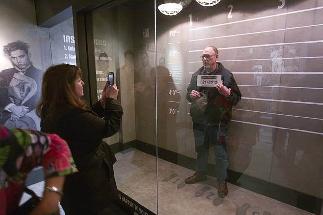 Patricia Brown of Anchorage, Alaska takes a photo of her husband Dave McMahan at the Mob Museum, the National Museum of Organized Crime and Law Enforcement, in downtown Las Vegas Wednesday, Feb.13, 2013. The museum celebrates it's first anniversary on Valentine's Day.