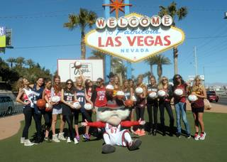 The 2013 Sports Illustrated Swimsuit Issue models in NCAA jerseys at the Welcome to Fabulous Las Vegas sign on Thursday, Feb. 14, 2013.