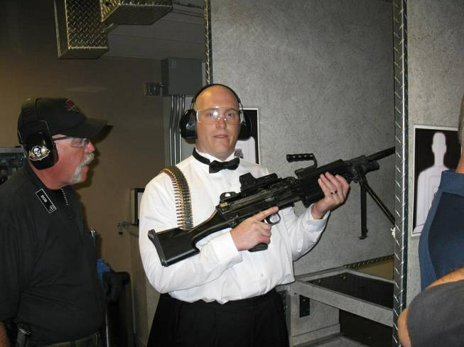 "This July 28, 2012, photo provided by Bob MacDuff shows MacDuff holding an automatic weapon at the Gun store in Las Vegas after his ""shotgun wedding."" One Las Vegas shooting range is selling ""take a shot at love"" packages that include 50 submachine gun rounds. Another is offering wedding packages in which the bride and groom can pose with Uzis and ammunition belts. And a third invites lovebirds to renew their vows and shoot a paper cutout zombie in the face."