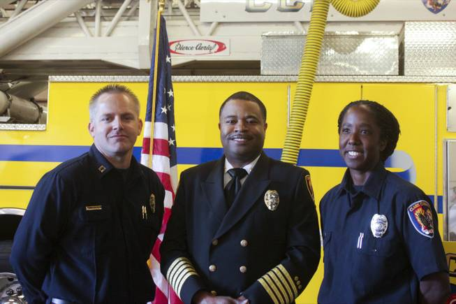 Newly promoted Fire Captain Darren Morville, left, and Fire Engineer Jennifer Osborne, right, pose for a picture with Clark County Fire Chief Bertral Washington after a ceremony honoring Osborne, Friday, Feb. 15, 2013. Osborne is the first black female to be promoted to Fire Engineer in the Clark County Fire Department.