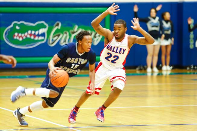 Chris Nelson of Canyon Springs attempts to run the ball past Ryan John of Valley HS score their championship game, Friday Feb. 15, 2013. Canyon Springs beat Valley 81 to 74 taking the Sunrise Championship for Division 1.