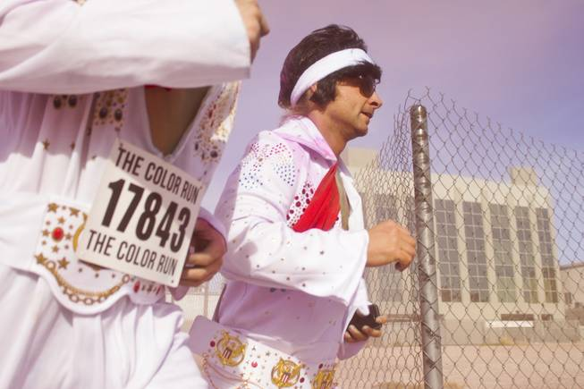 Two participants dressed as Elvis round the corner after passing the pink stage of the 5K Color Run, Saturday, Feb. 16, 2013.
