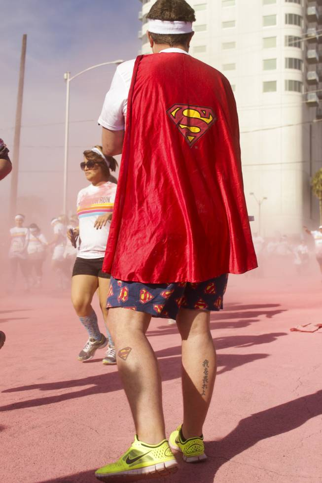 A participant wearing a superman cape and shorts with a superman tattoo on his left calf waits after passing the pink stage of the 5K Color Run, Saturday, Feb. 16, 2013.