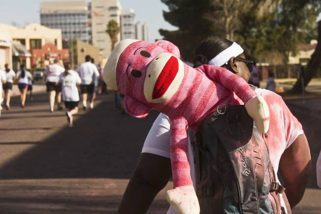 A red striped sock monkey hangs out of a participants backpack at the 5K Color Run, Saturday, Feb. 16, 2013.