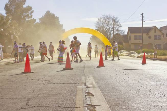 Participants come out of a yellow haze as they pass through the yellow stage of the 5K Color Run, Saturday, Feb. 16, 2013.